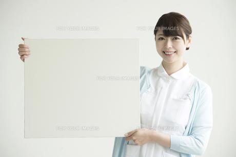 メッセージボードを持ち微笑む看護師の写真素材 [FYI00491413]