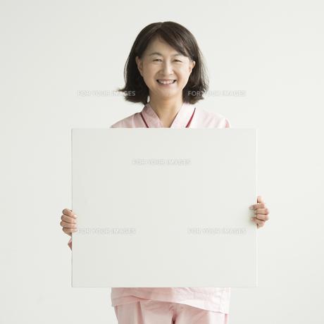 メッセージボードを持ち微笑む患者の写真素材 [FYI00491417]