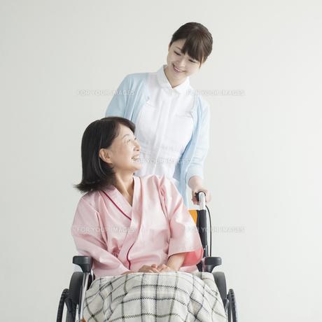 車椅子に乗る患者と話をする看護師の写真素材 [FYI00491418]