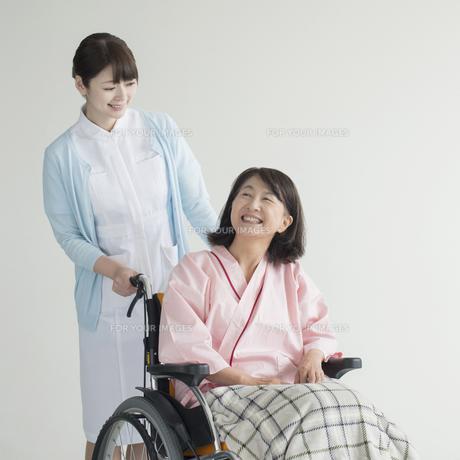 車椅子に乗る患者と話をする看護師の素材 [FYI00491419]