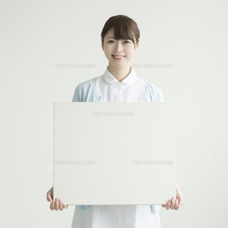 メッセージボードを持ち微笑む看護師の写真素材 [FYI00491421]