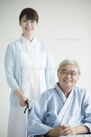 患者の乗る車椅子を押す看護師の素材 [FYI00491425]