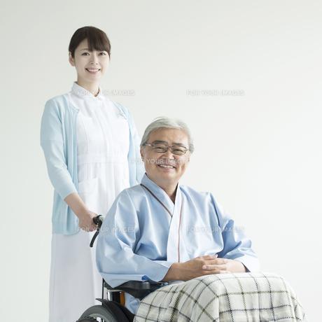 患者の乗る車椅子を押す看護師の素材 [FYI00491444]