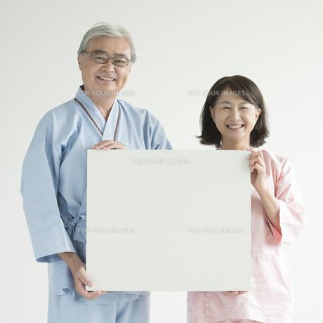 メッセージボードを持ち微笑む患者の写真素材 [FYI00491445]