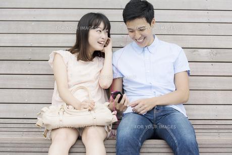 スマホを見るカップルの素材 [FYI00491460]