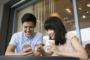 カフェでスマホを使うカップルの素材 [FYI00491494]