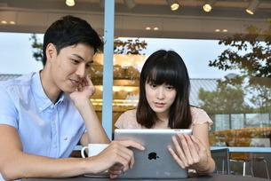 カフェでタブレットを使うカップルの素材 [FYI00491497]