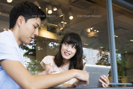 カフェでタブレットを使うカップルの素材 [FYI00491498]