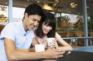 カフェでスマホを見るカップルの素材 [FYI00491499]