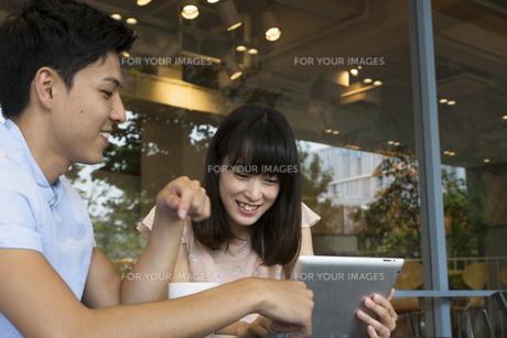 カフェでタブレットを使うカップルの素材 [FYI00491500]
