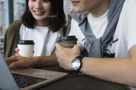カフェでパソコンを見るカップルの素材 [FYI00491507]