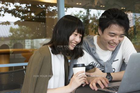 カフェでパソコンを見るカップルの素材 [FYI00491509]