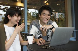 カフェでパソコンを見るカップルの素材 [FYI00491510]