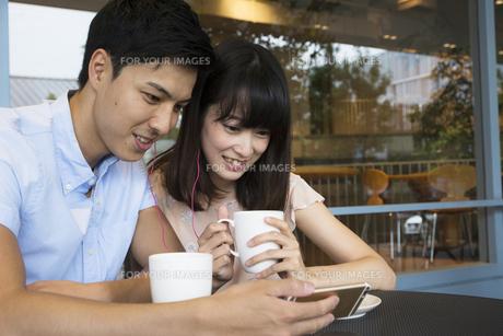 カフェでスマホを見るカップルの素材 [FYI00491512]