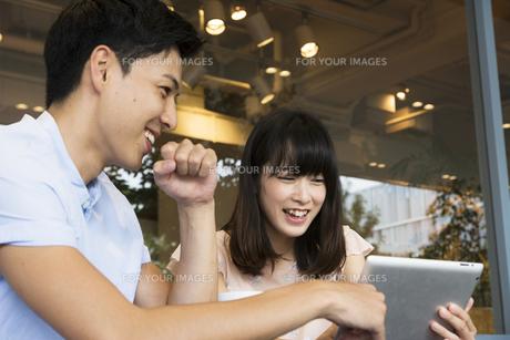 カフェでタブレットを使うカップルの素材 [FYI00491513]