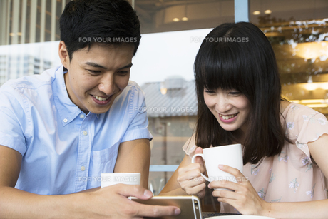 カフェでスマホを見るカップルの素材 [FYI00491514]