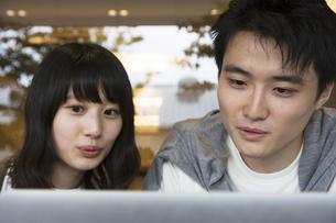 カフェでパソコンを見るカップルの素材 [FYI00491515]