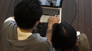 カフェでパソコンを見るカップルの素材 [FYI00491517]
