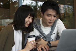 カフェでパソコンを見るカップルの素材 [FYI00491519]