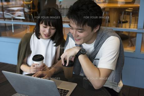 カフェでパソコンを見るカップルの素材 [FYI00491520]