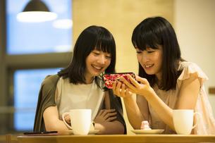 カフェでスマホを見る女性2人の素材 [FYI00491550]