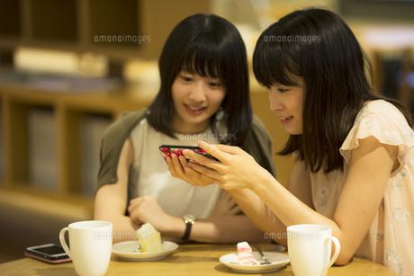 カフェでスマホを見る女性2人の素材 [FYI00491551]