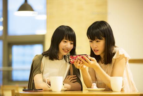 カフェでスマホを見る女性2人の素材 [FYI00491559]