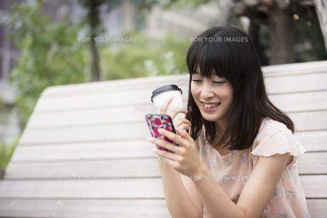 スマホを見る笑顔の女性の素材 [FYI00491594]