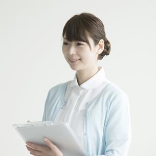 カルテを持ち微笑む看護師の写真素材 [FYI00491734]