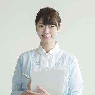 カルテを持ち微笑む看護師の写真素材 [FYI00491782]