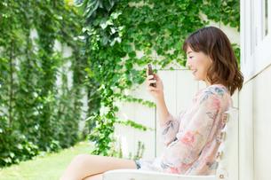 ベンチで携帯電話を使う女性の写真素材 [FYI00494259]