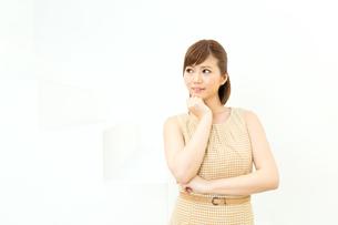 白い壁に立つ女性の写真素材 [FYI00495205]