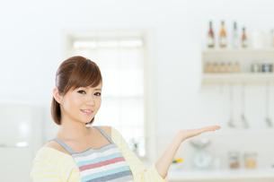 ダイニングで案内する若い主婦の写真素材 [FYI00495268]