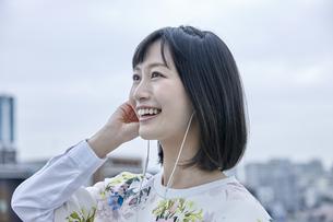 音楽を聴く笑顔の女性の素材 [FYI00495559]