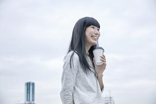 コーヒーを飲む笑顔の女性の素材 [FYI00495562]