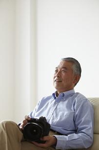 ソファに座りカメラを持つシニア男性の写真素材 [FYI00496294]