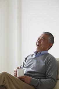 ソファに座りカップを持つシニア男性の写真素材 [FYI00496297]