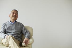 ソファに座る笑顔のシニア男性の写真素材 [FYI00496300]