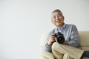 ソファに座りカメラを持つシニア男性の写真素材 [FYI00496304]