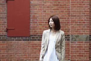 レンガの壁の前に立つ女性の写真素材 [FYI00496313]