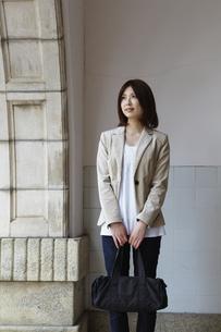 壁の前に立つ女性の写真素材 [FYI00496318]