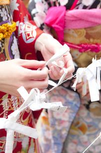 おみくじを結ぶ女性の手元 宮城県塩釜市の素材 [FYI00496450]