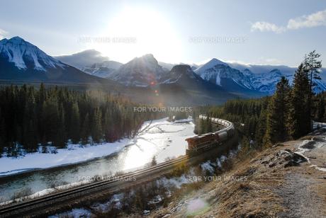冬のカナディアン・ロッキー ボウ川沿いを走る貨物列車の写真素材 [FYI00497118]