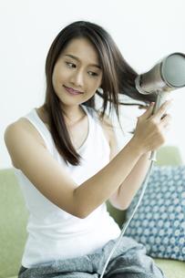 ドライヤーで髪を乾かす若い女性の写真素材 [FYI00497334]