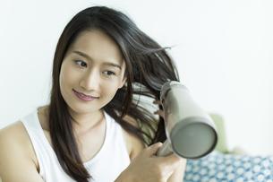 ドライヤーで髪を乾かす若い女性の写真素材 [FYI00497337]