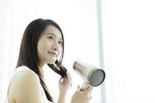 ドライヤーで髪を乾かす若い女性の写真素材 [FYI00497338]