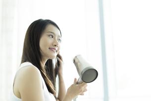 ドライヤーで髪を乾かす若い女性の写真素材 [FYI00497339]