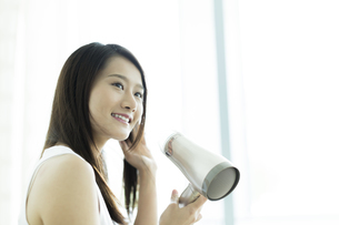ドライヤーで髪を乾かす若い女性の写真素材 [FYI00497340]