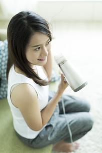 ドライヤーで髪を乾かす若い女性の写真素材 [FYI00497341]