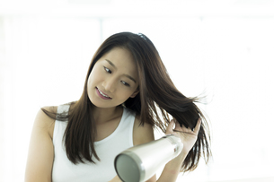 ドライヤーで髪を乾かす若い女性の写真素材 [FYI00497342]